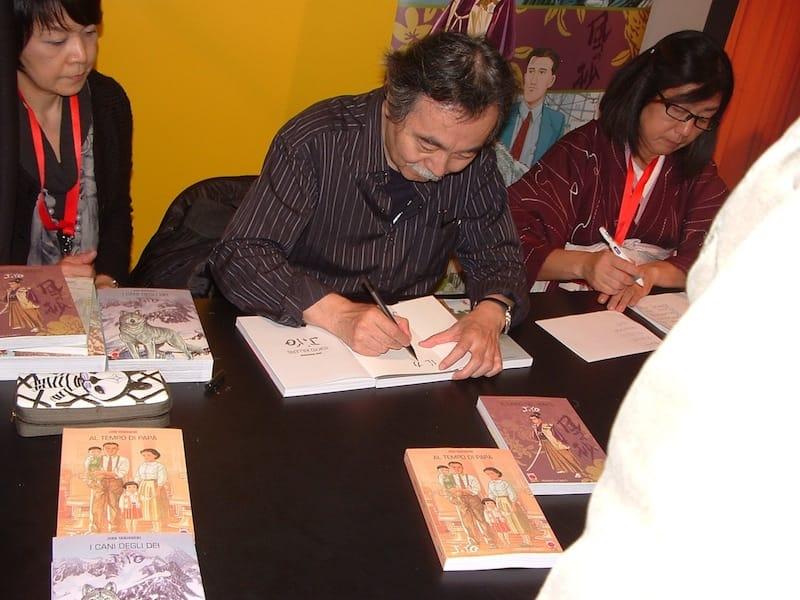 Jiro Taniguchi mentre disegna e firma autografi © Ma.Be.