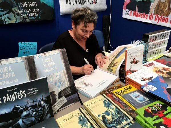 LA SIGNORA DEL FUMETTO ITALIANI: LAURA SCARPA, mentre disegna allo stand ComicOut