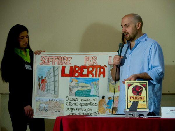Paolo Castaldi dialoga con gli studenti mentre guarda i loro lavori su cartoncini.