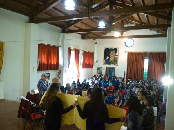Paolo Castaldi dialoga con gli studenti mentre guarda i loro lavori su cartoncini. vista al palco verso gli studenti in paltea