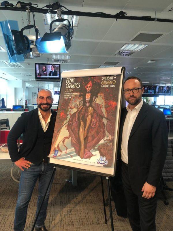 Foto del direttore di Etna Comics,   Antonio Mannino, insieme con il giornalista Vittorio Eboli, e nel mezzo il Manifesto della nona edizione del Festival Internazionale del Fumetto e della Cultura Pop.