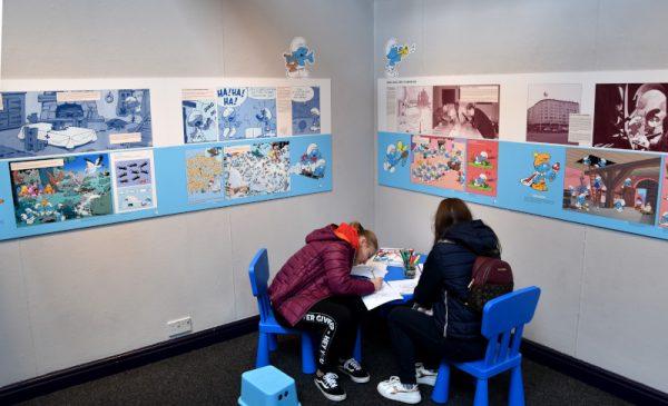 Scorcio della mostra dedicata ai 60 anni dei Puffi con due ragazze che disegnano sul tavolo lasciato libero dalla staff.