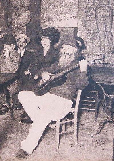 """Il proprietario con la chitarra che indossa un cappello si riferisce ancora a Frédérick Gérard, soprannominato Le Pere Frédé (""""Padre Fede"""", come del resto chiama se stesso nella pagina successiva). Qui lui in un bar. Immagine 12 di 23"""