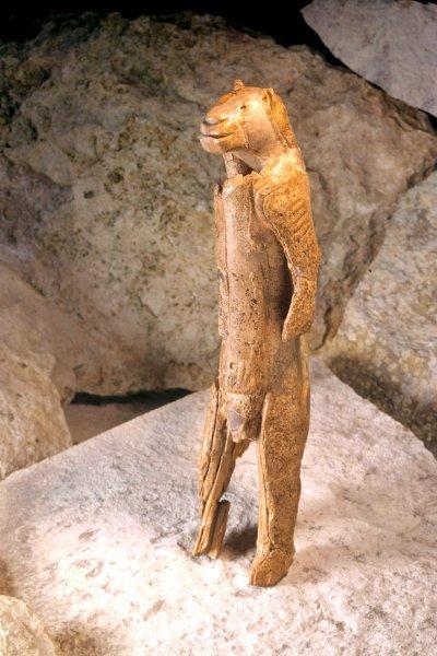 Sul tavolo in primo piano ella ha (presumibilmente una copia) un Löwenmensch (uomo leone/leone maschio), trovato nella Grotta di Stadel, nella Germania Meridionale. Risalente a circa 40.000 anni fa, è il più antico esempio del mondo di arte figurativa e, si, è antropomorfa. I popoli hanno raccontato storie su personaggi antropomorfi da quando si raccontano storia, e ci sono molti altri esempi preistorici, comprese molte pitture rupestri. E' ricavata da un zanna di mammuth lanoso ed è alta 31 centimetri. E' oggetto di discussione se la figura con testa di leone sia maschio o femmina.